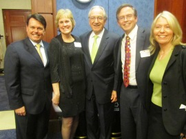 Five individuals standing with Senator Tom Harkin in the middle flanked on his left by Tom Sheridan, Julie Freed, and on his right by Jim Fruchterman and Betsy Beaumon, standing, all in dark suits,